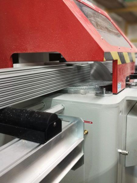 Fase di lavorazione di una tapparella in alluminio mentre viene tagliata alla troncatrice